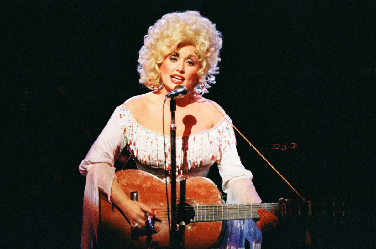 Dolly Parton Performs At The Dominion Theatre in London. She's playing the guitar and singing into a microphone.