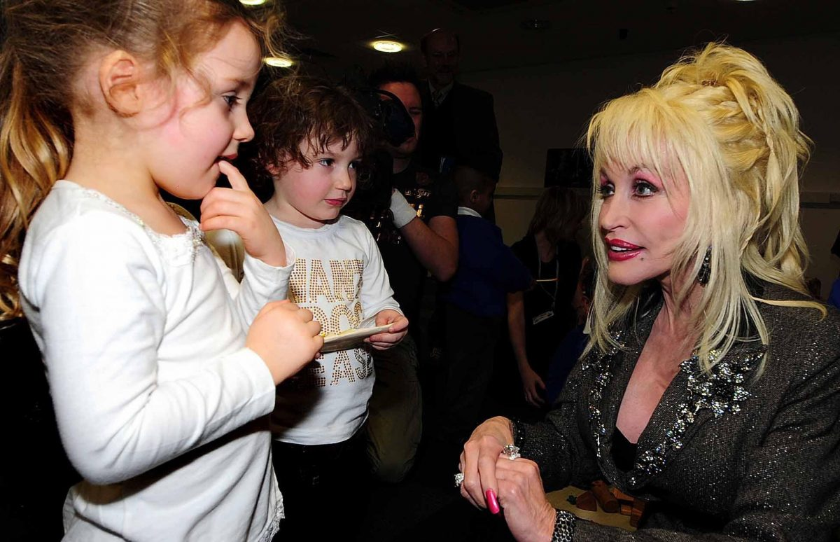 Dolly Parton crouches down to speak with two children.