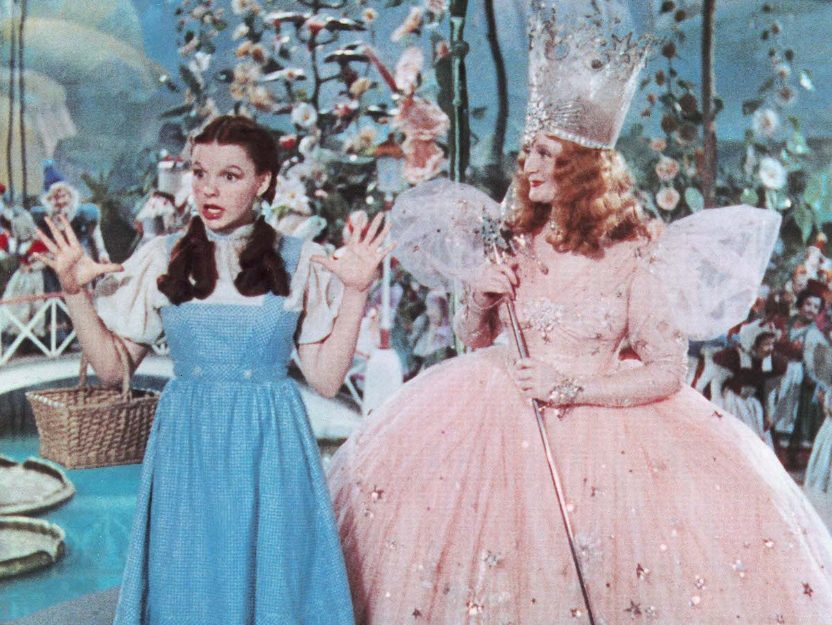Judy Garland raises her hands while speaking as a smiling Billie Burke looks on in 'The Wizard of Oz'