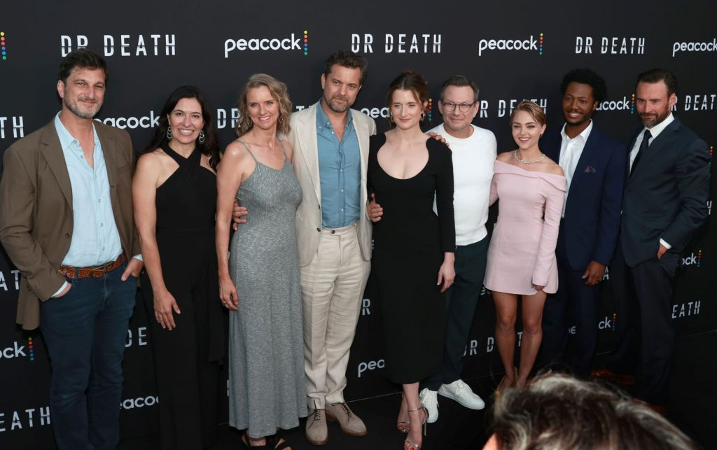 Nine cast members from 'Dr. Death' are dressed professionally standing in front of a black background with Dr. Death and Peacock written on it.