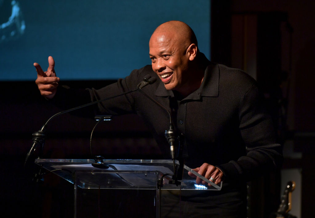 Dr. Dre speaks on stage at a Grammy event. He's dressed in all black.