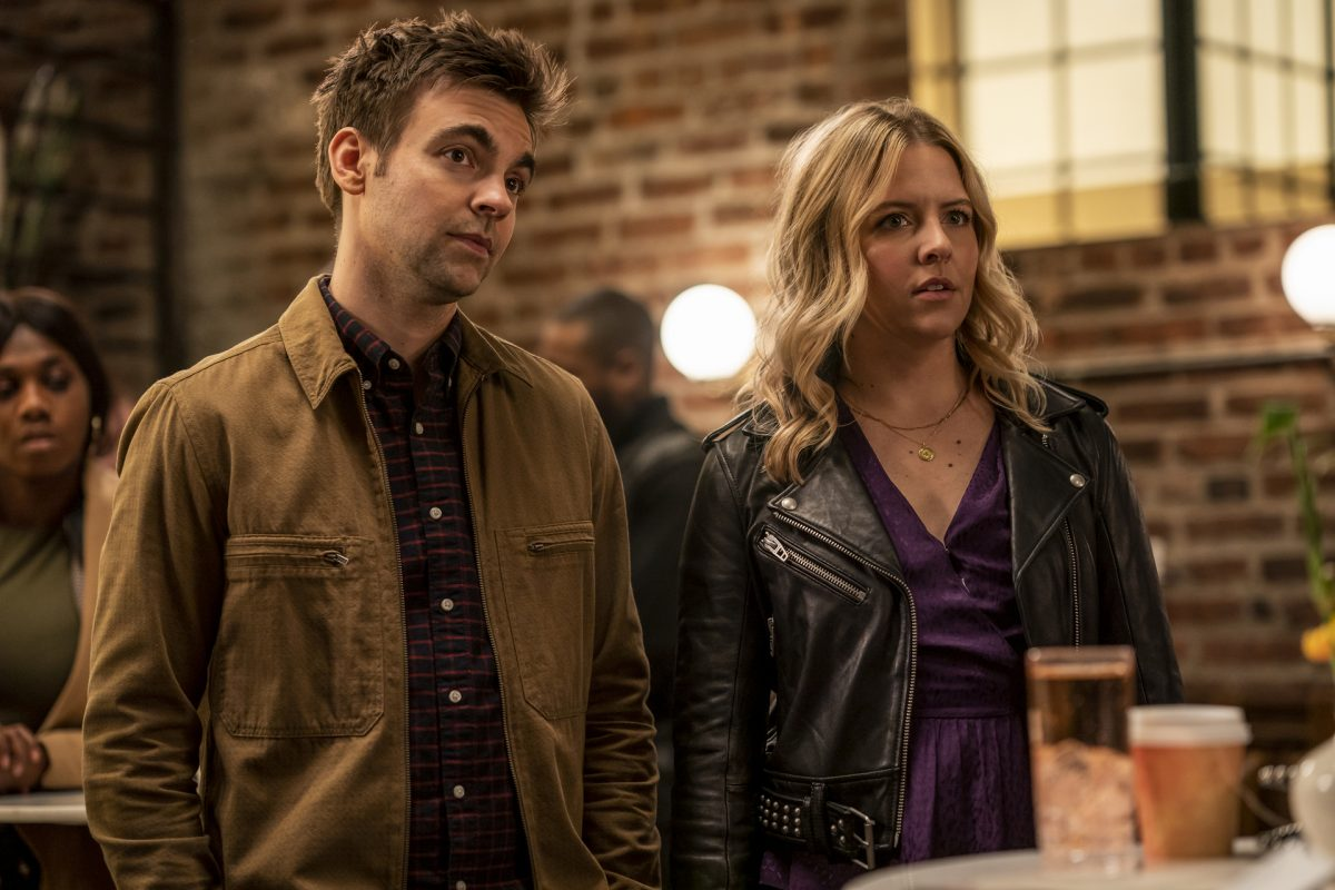 Drew Tarver and Heléne Yorke stand in a bar with brick walls in 'The Other Two.'