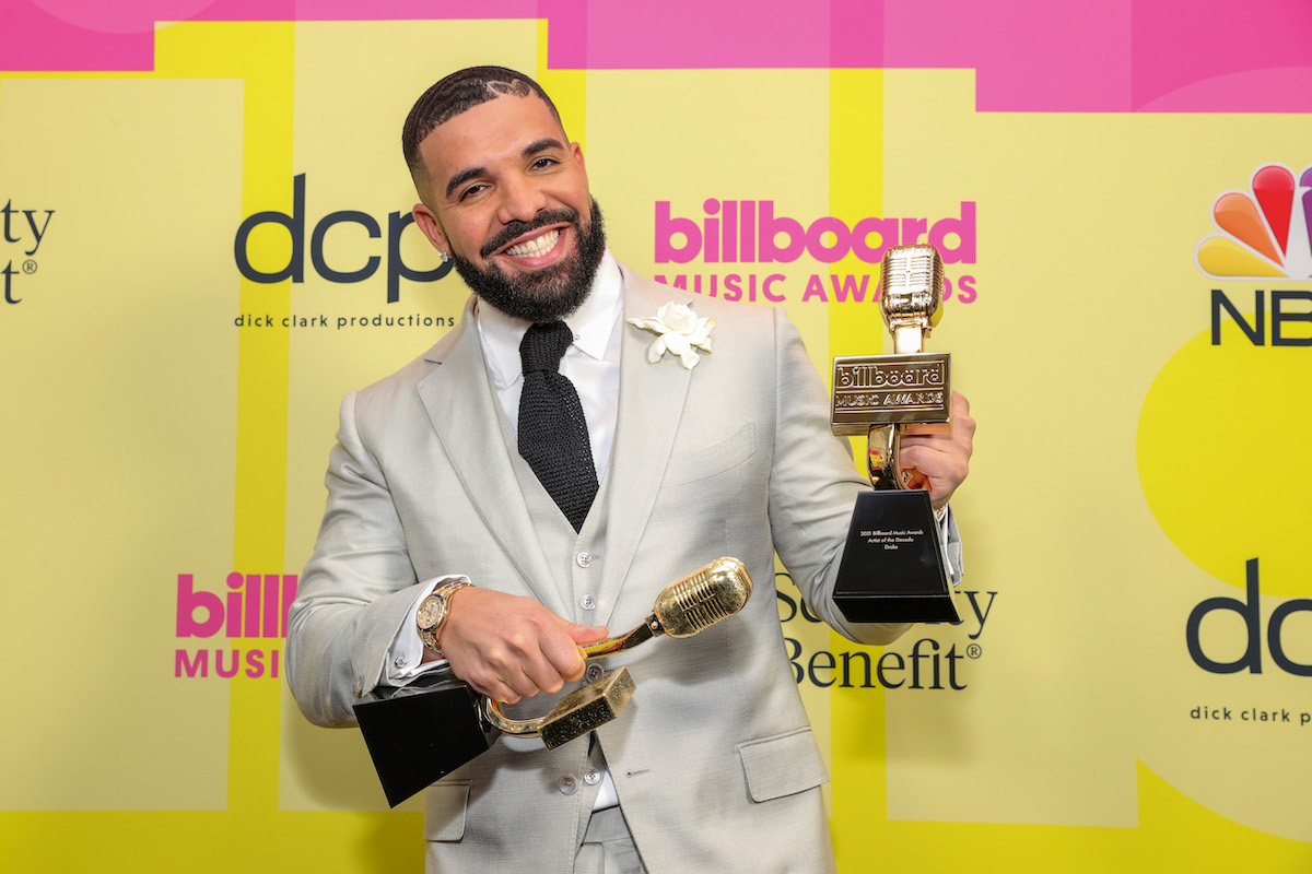 Drake poses with awards in a cream suit while smiling as winner of the Artist of the Decade Award, poses backstage for the 2021 Billboard Music Awards, broadcast on May 23, 2021 at Microsoft Theater in Los Angeles, California.