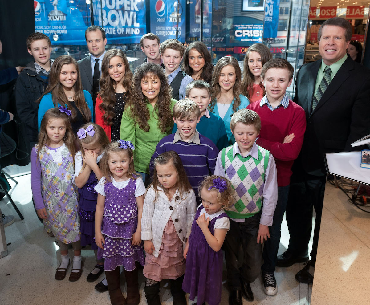 The Duggar family, including Josh Duggar, crowded together and smiling at the camera on the set of 'Extra' to discuss Duggar news