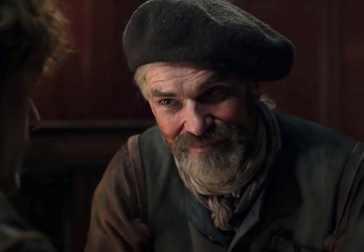 Duncan Lacroix as Murtagh Fitzgibbons in 'Outlander.' He sits in a room with brown wooden walls. He wears colonial clothes with a grey cap, his grey hair in a low ponytail. Lacroix played Murtagh for four seasons of 'Outlander,' and fans are wondering if he'll be in the 'Outlander' Season 6 cast.