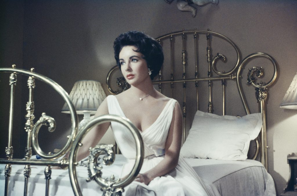 Elizabeth Taylor looking off to the side, seated on a bed, in 'Cat on a Hot Tin Roof'