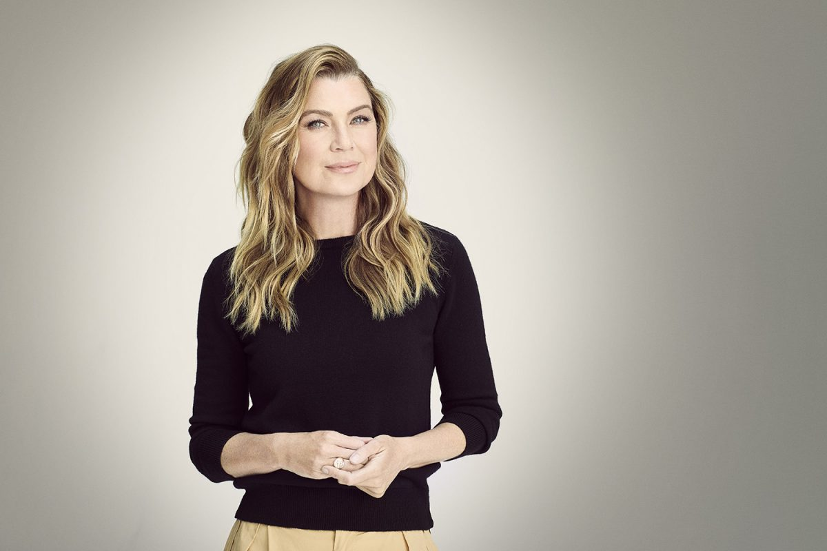 Grey's Anatomy star Ellen Pompeo wearing a black top and beige pants and wearing her blonde hair down. She's standing in front of a solid grey background and staring at the camera.