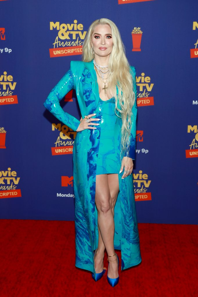 Erika Jayne in a tie dye blue dress and matching trench coat, posing and smiling for the camera at an event.