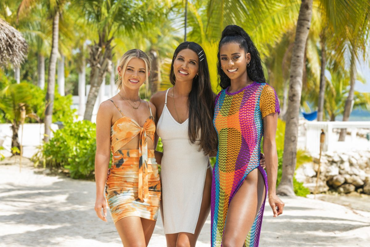 'FBoy Island' contestants Sarah Emig, CJ Franco, and Nakia Renee stand in front of a tropical background.