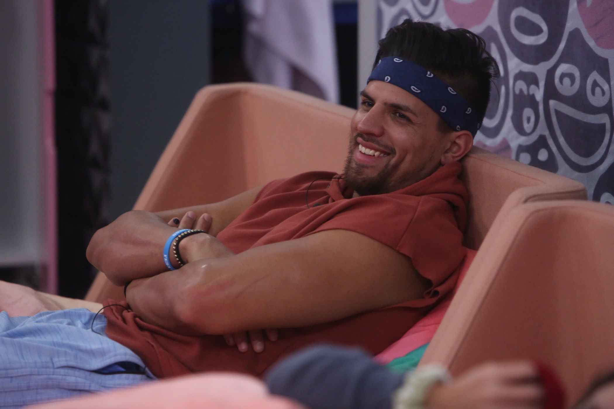 Fessy Shafaat, part of MTV's 'The Challenge' Season 37 cast, laughing while sitting on a couch in the 'Big Brother' house