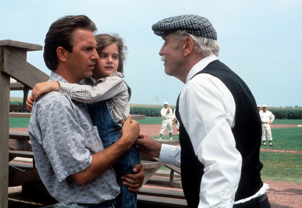 Kevin Costner holds Gaby Hoffmann while talking to Burt Lancaster in front of the field in 'Field of Dreams' in 1989
