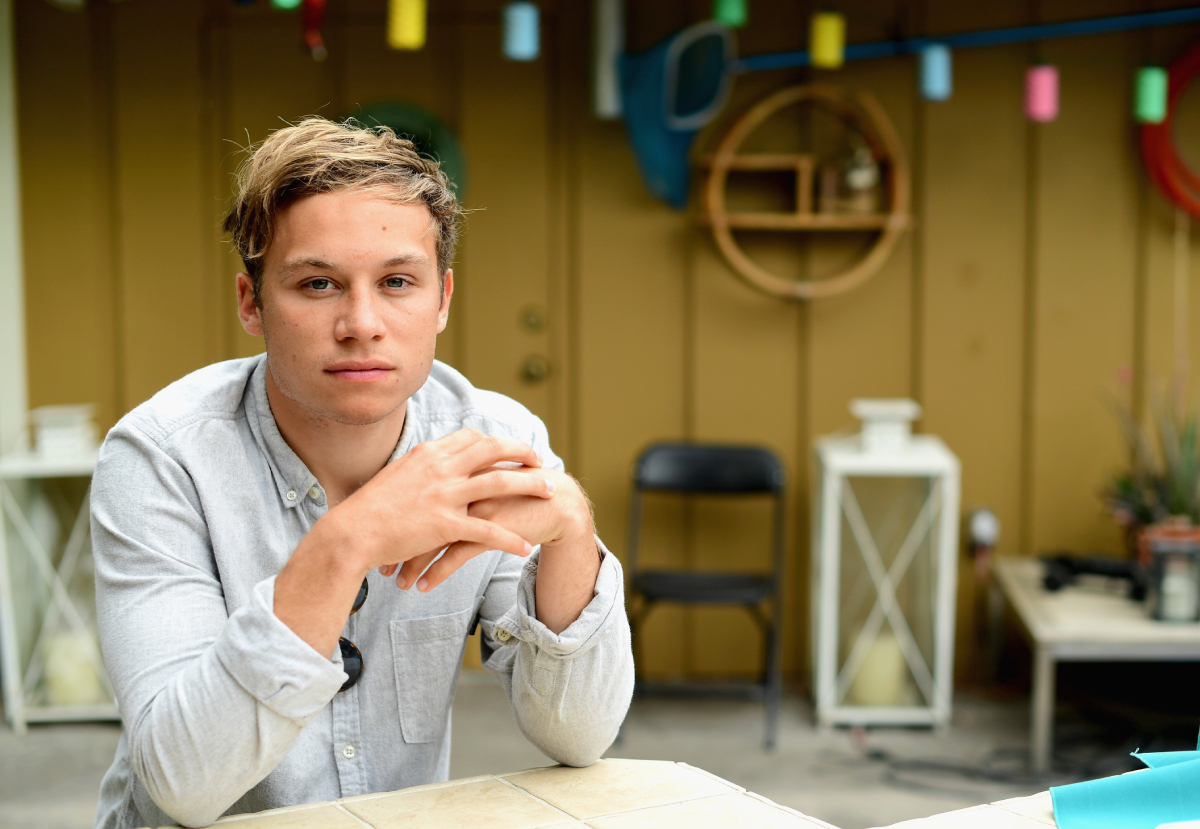Finn Cole in a grey button-down sitting with his hands folded on a table.