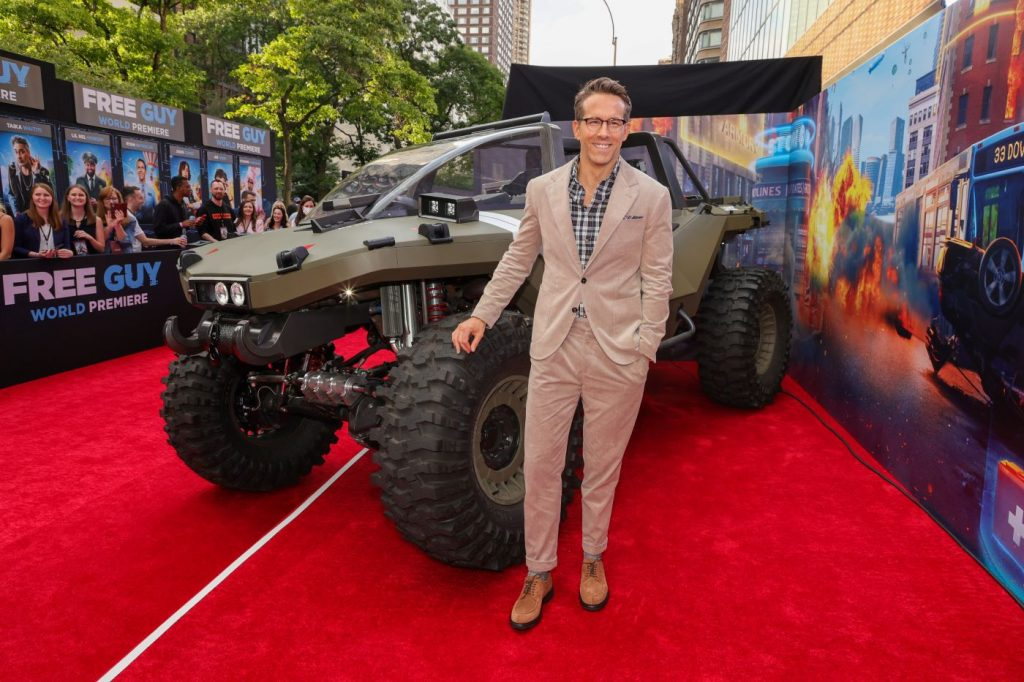Ryan Reynolds standing in front of an army green truck on the red carpet at a movie premiere wearing a tan suit with a blue undershirt.