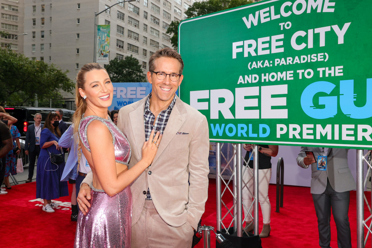 Blake Lively and Ryan Reynolds pose on the red carpet in front of a sign welcoming guests to the 'Free Guy' premiere