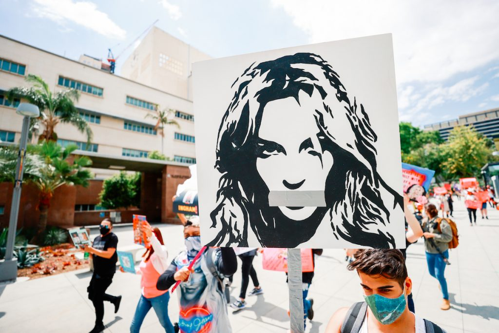 People carrying a Britney Spears image in outdoor rally