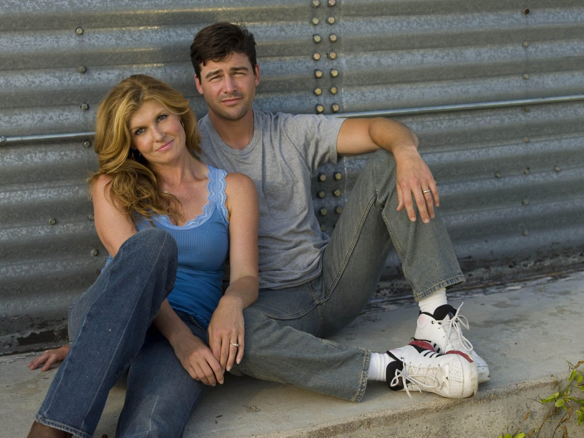 Connie Britton as Tami Taylor and Kyle Chandler as Eric Taylor pose for a promotional photo for season 1 of 'Friday Night Lights'