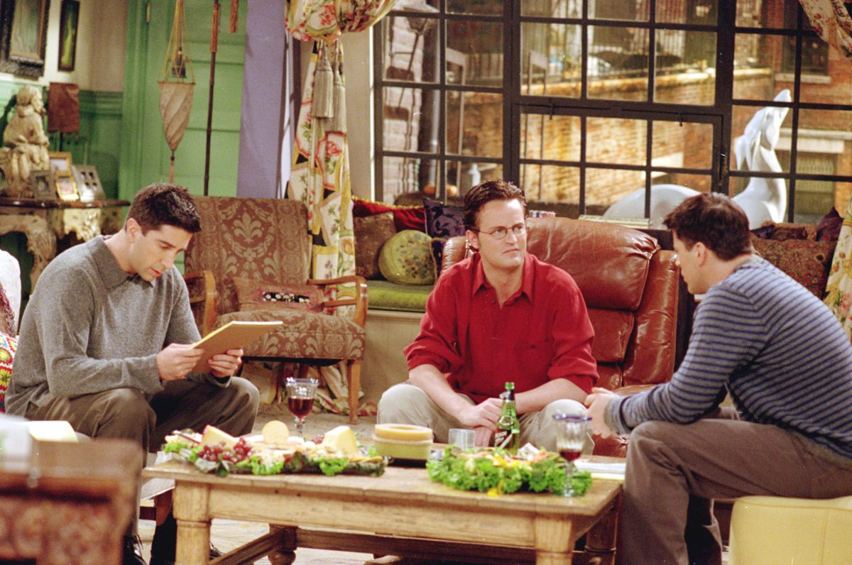 Ross Geller, Chandler Bing and Joey Tribbiani chat while sitting in the living room of Monica's apartment during a scene in 'Friends'