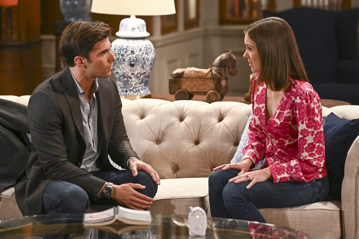 Josh Swickard and Katelyn MacMullen sitting on a couch facing each other on the set of 'General Hospital