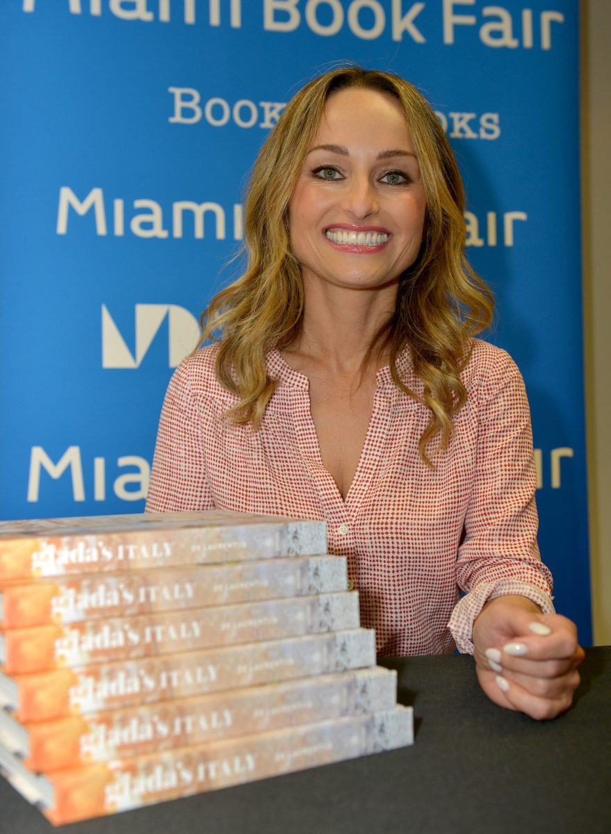 Giada De Laurentiis smiles as she sits next to a stack of her 'Giada's Italy' cookbooks