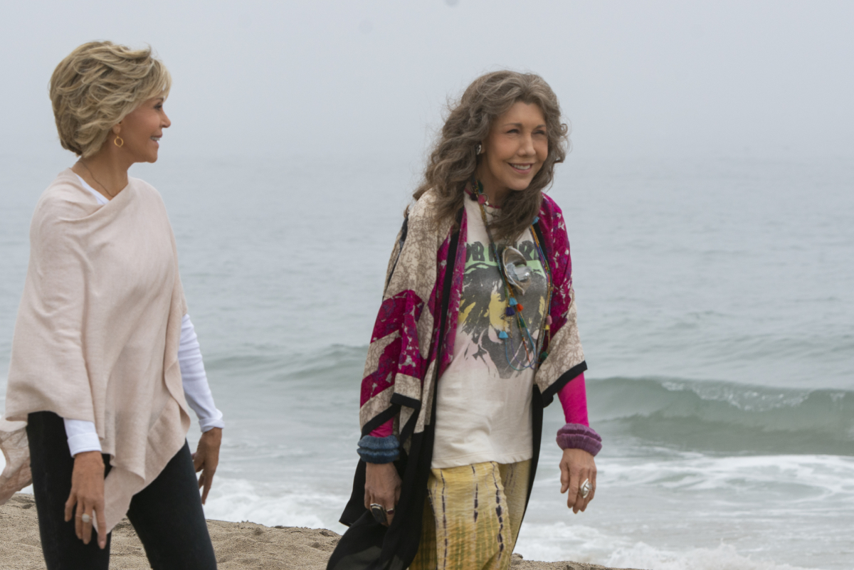Grace and Frankie smile and walk along the beach.