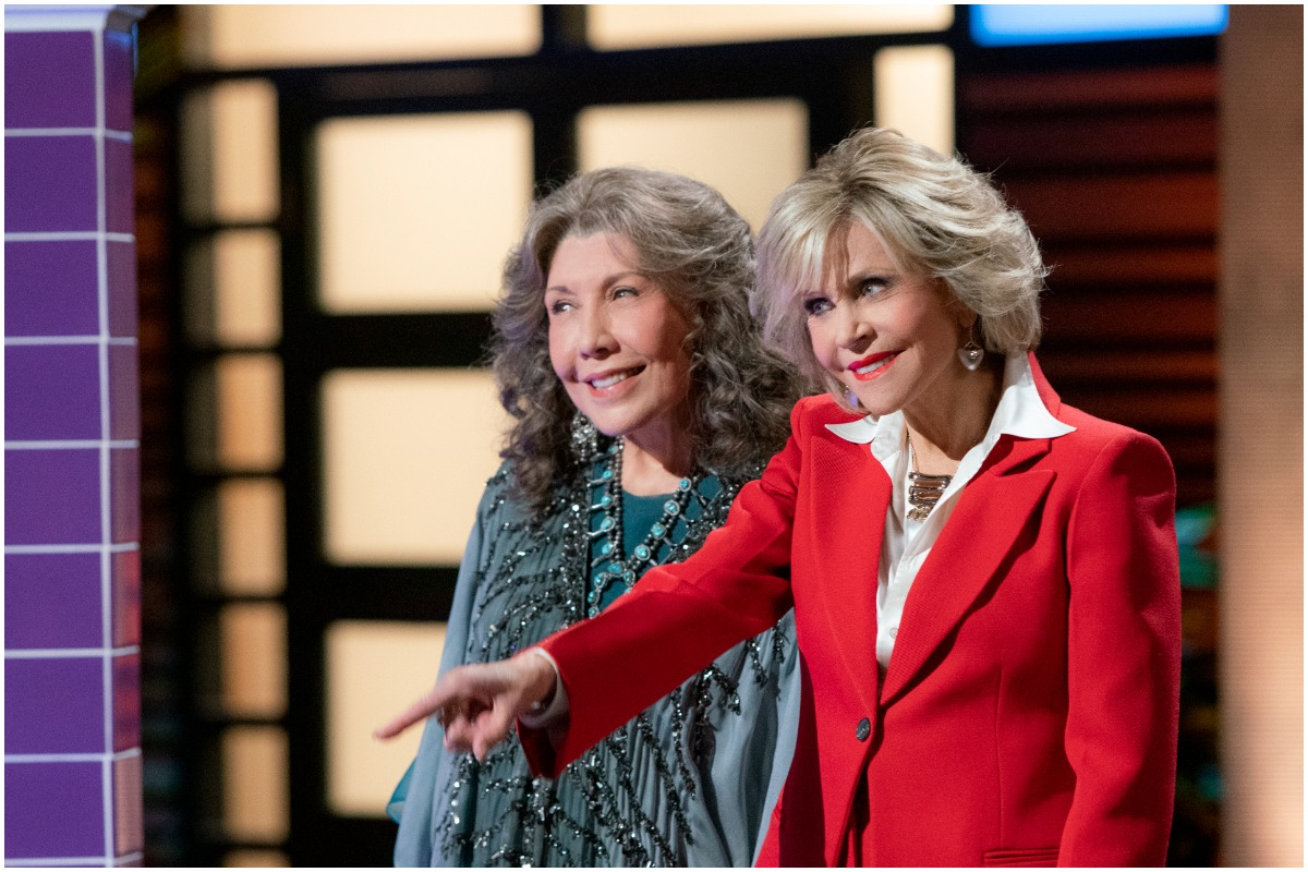 Grace and Frankie pitch a business idea. Grace wears a red suit and Frankie wears a blue parka.