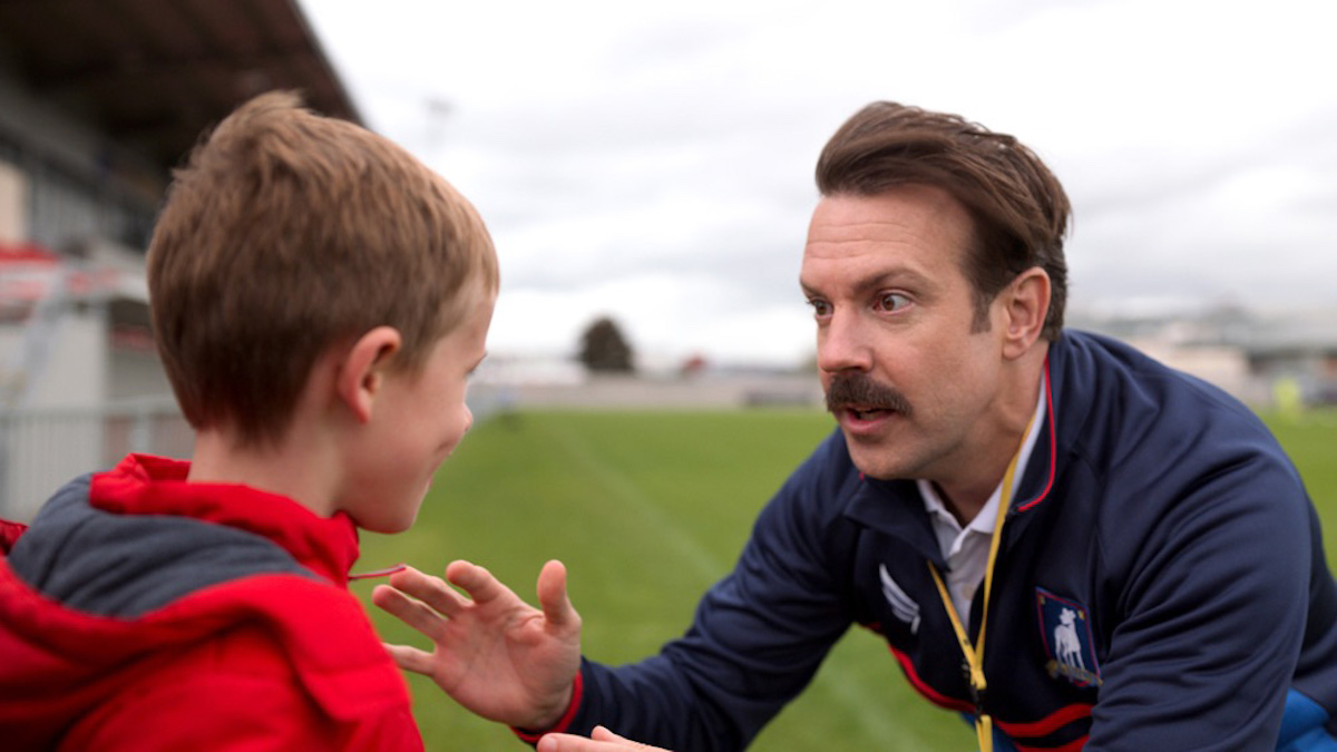 Jason Sudeikis wears a blue shirt and talks to Gus Turner on a soccer field in 'Ted Lasso' Season 1