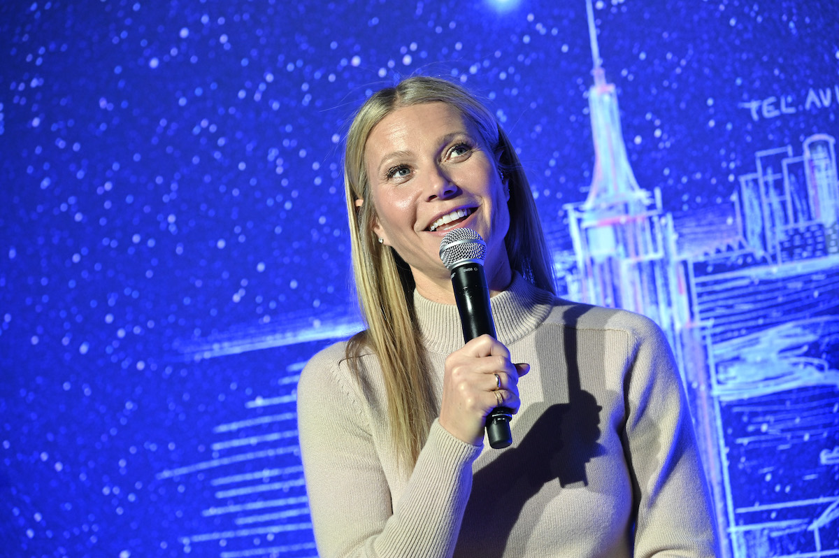 Gwyneth Paltrow holds a microphone and speaks on stage