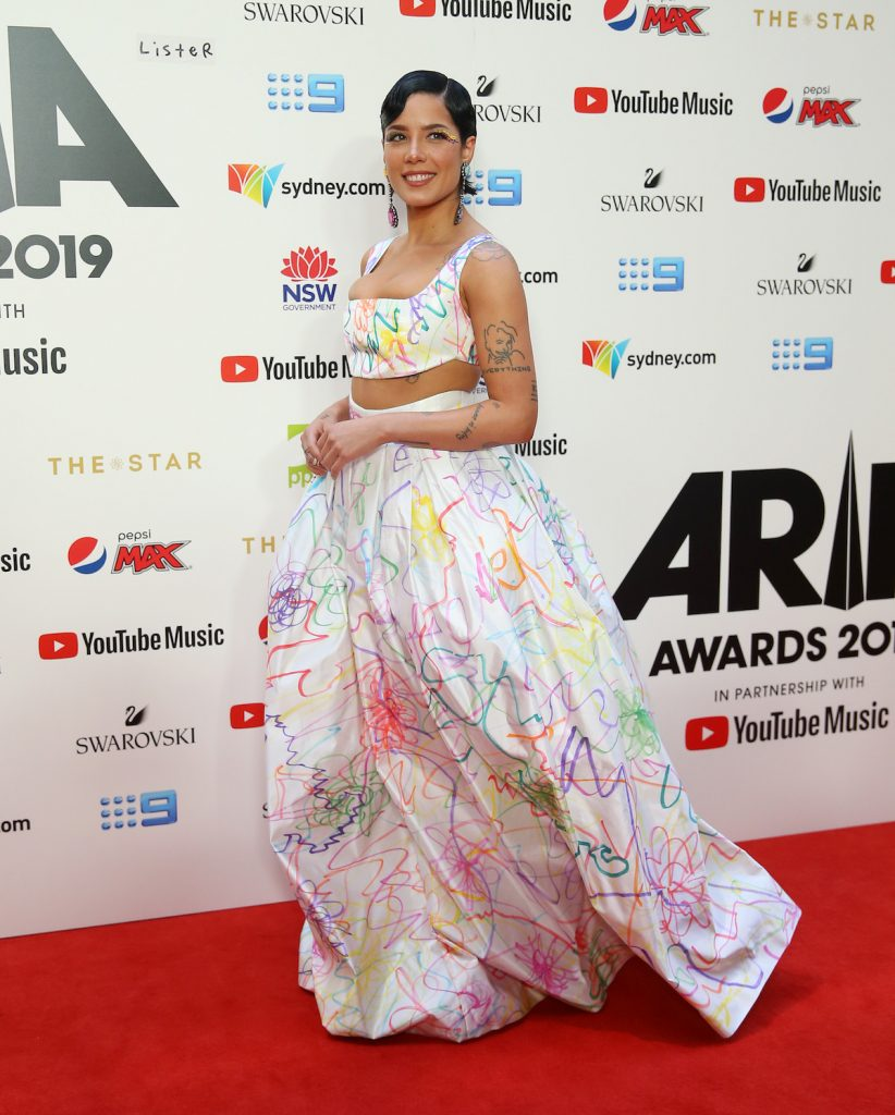 Halsey walks the red carpet in a long white gown covered in colorful designs.