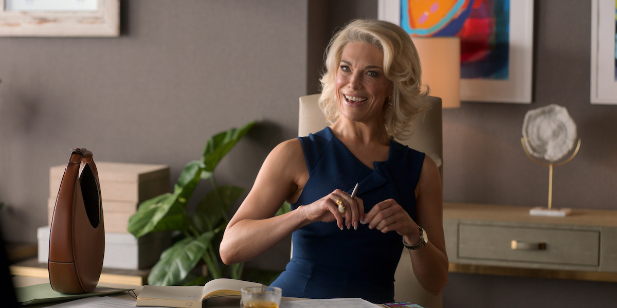 Hannah Waddingham smiles in a blue dress sitting at a desk in 'Ted Lasso' Season 2