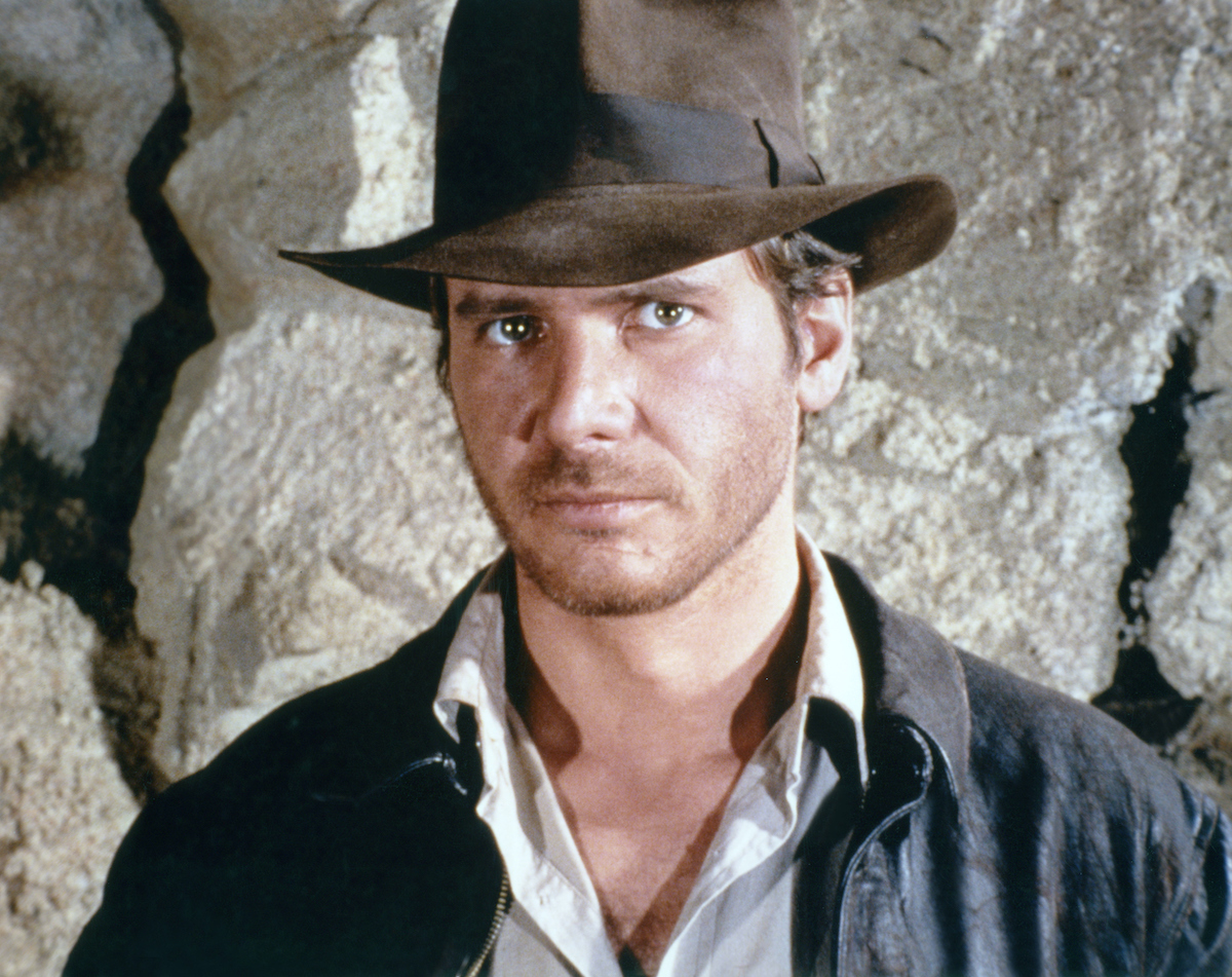 Harrison Ford wears a brown fedora and poses as Indiana Jones