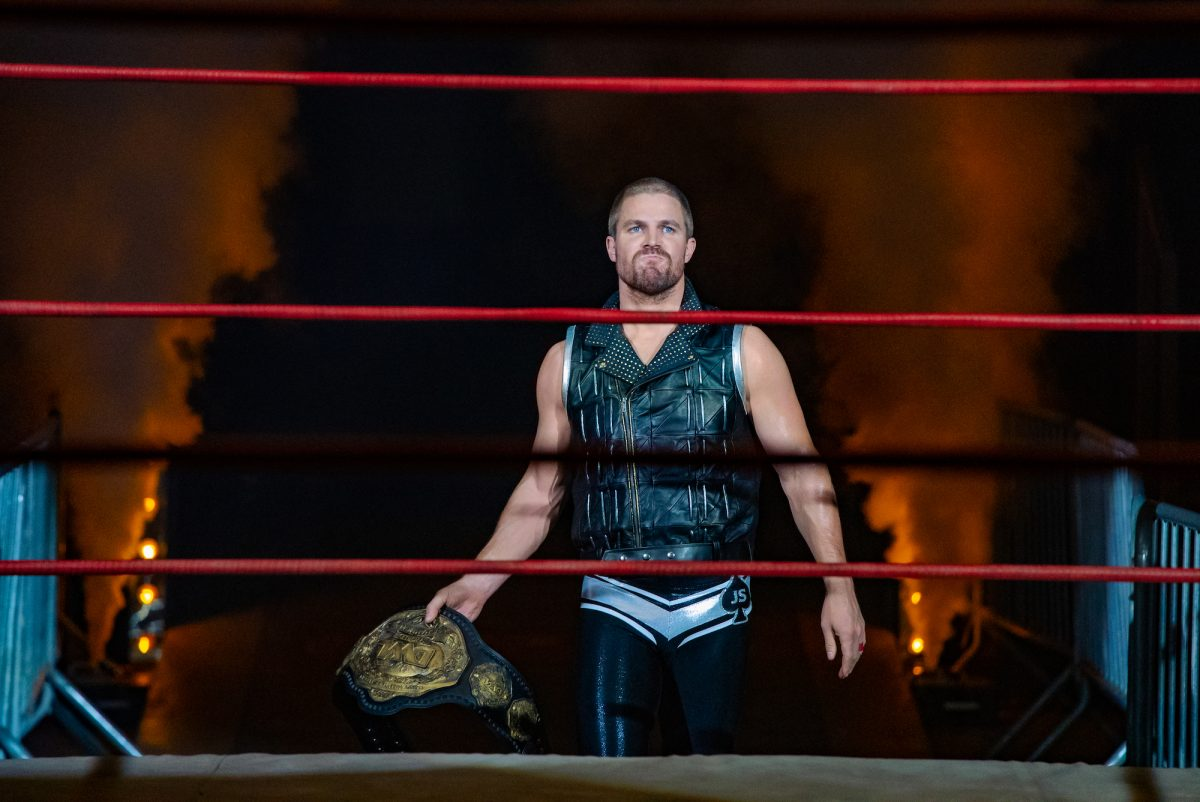 Heels: Stephen Amell carries the belt into the ring