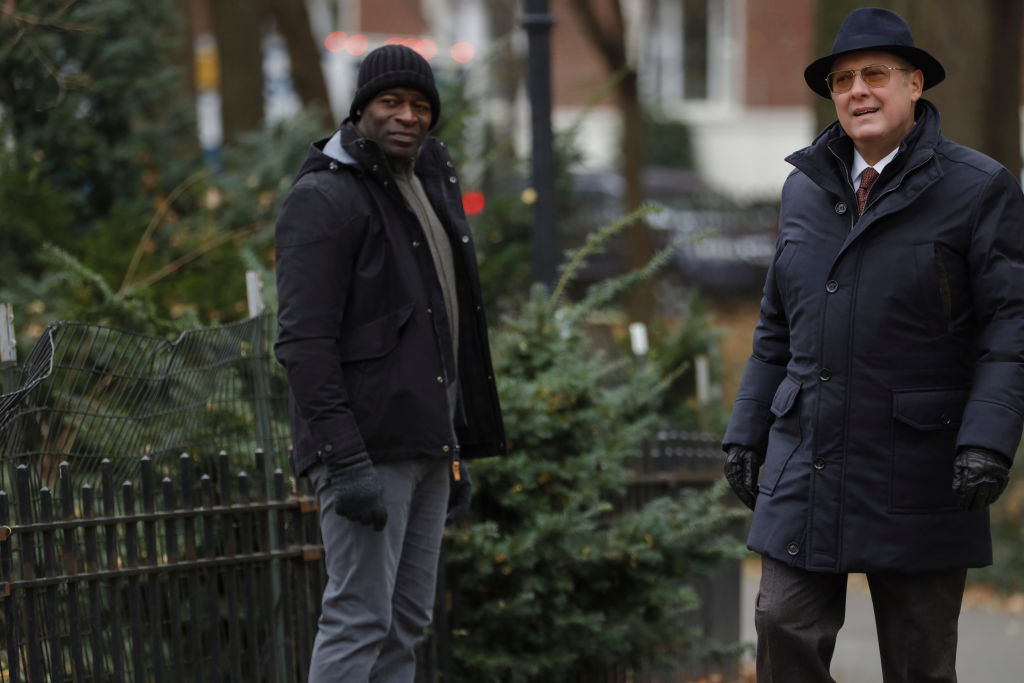 Hisham Tawfiq as Dembe Zuma, James Spader as Raymond 'Red' Reddington stand outside. Both are dressed in winter gear.