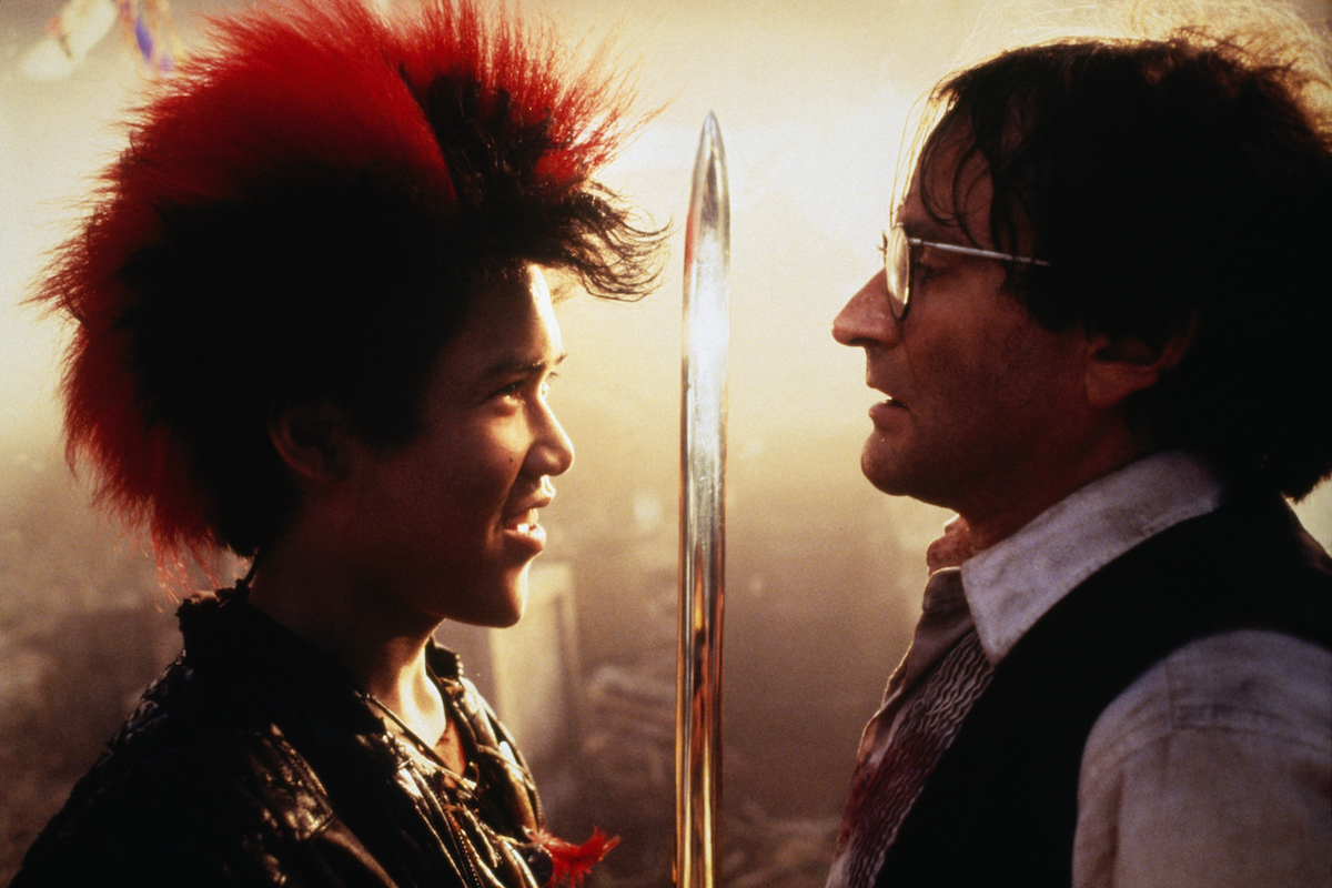 Dante Basco holds up a sword and smiles in front of Robin Williams in 'Hook'
