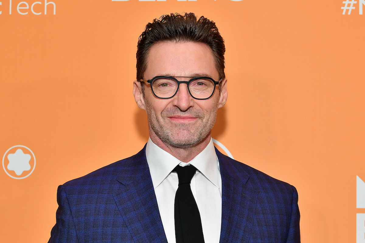 Hugh Jackman wears a suit and glasses as he poses