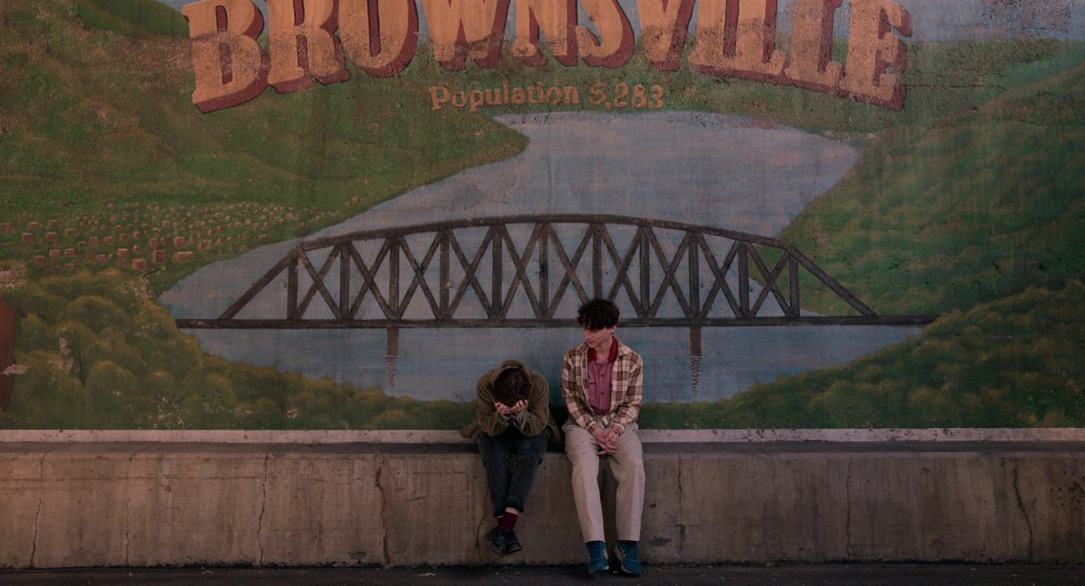 Sophia Lillis as Sydney Novak and Wyatt Oleff as Stanley Barber sit in front of the Brownsville sign in 'I Am Not Okay With This'