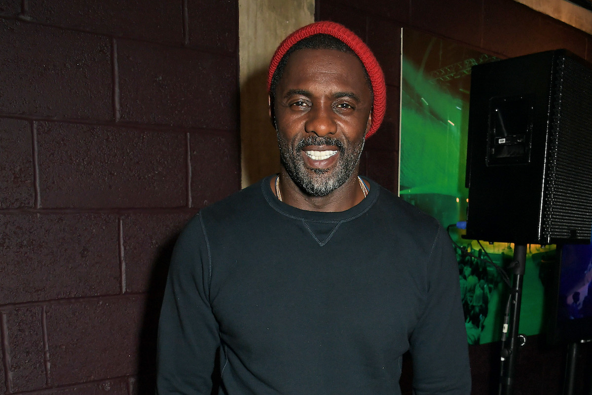 Idris Elba wears a black shirt and red hat as he smiles and poses