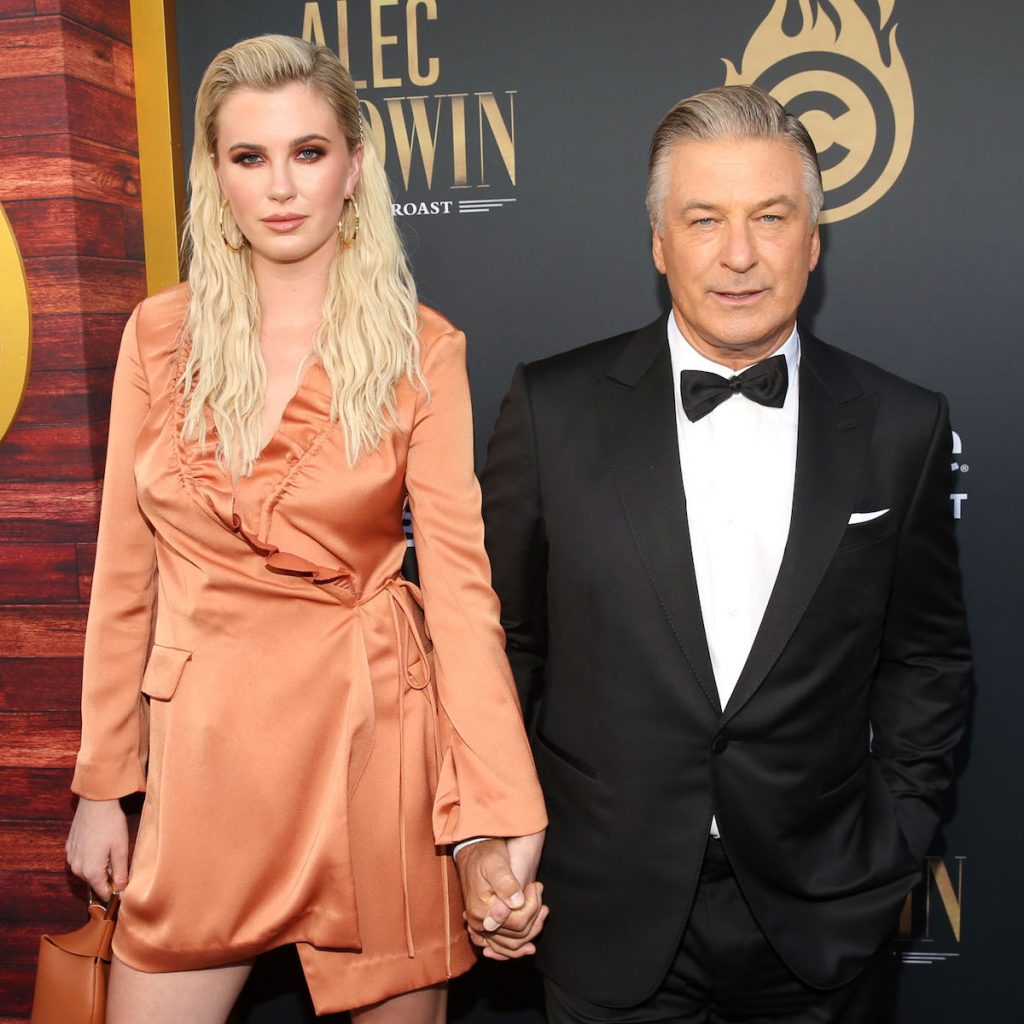 Ireland Baldwin and father Alec Baldwin pose for the camera holding hands at an event.