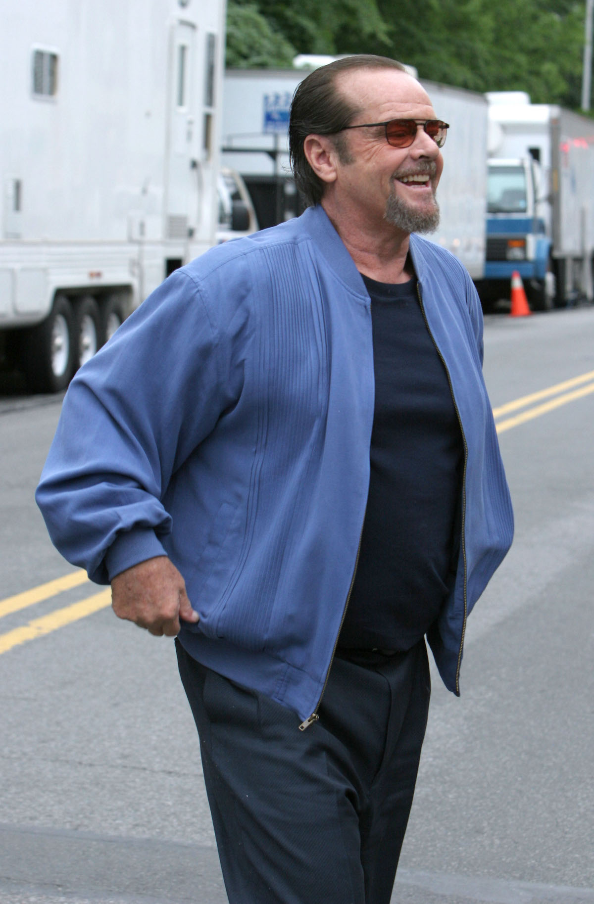 Jack Nicholson smiles wearing sunglasses, jeans, and a blue jacket on location for 'The Departed' in 2005