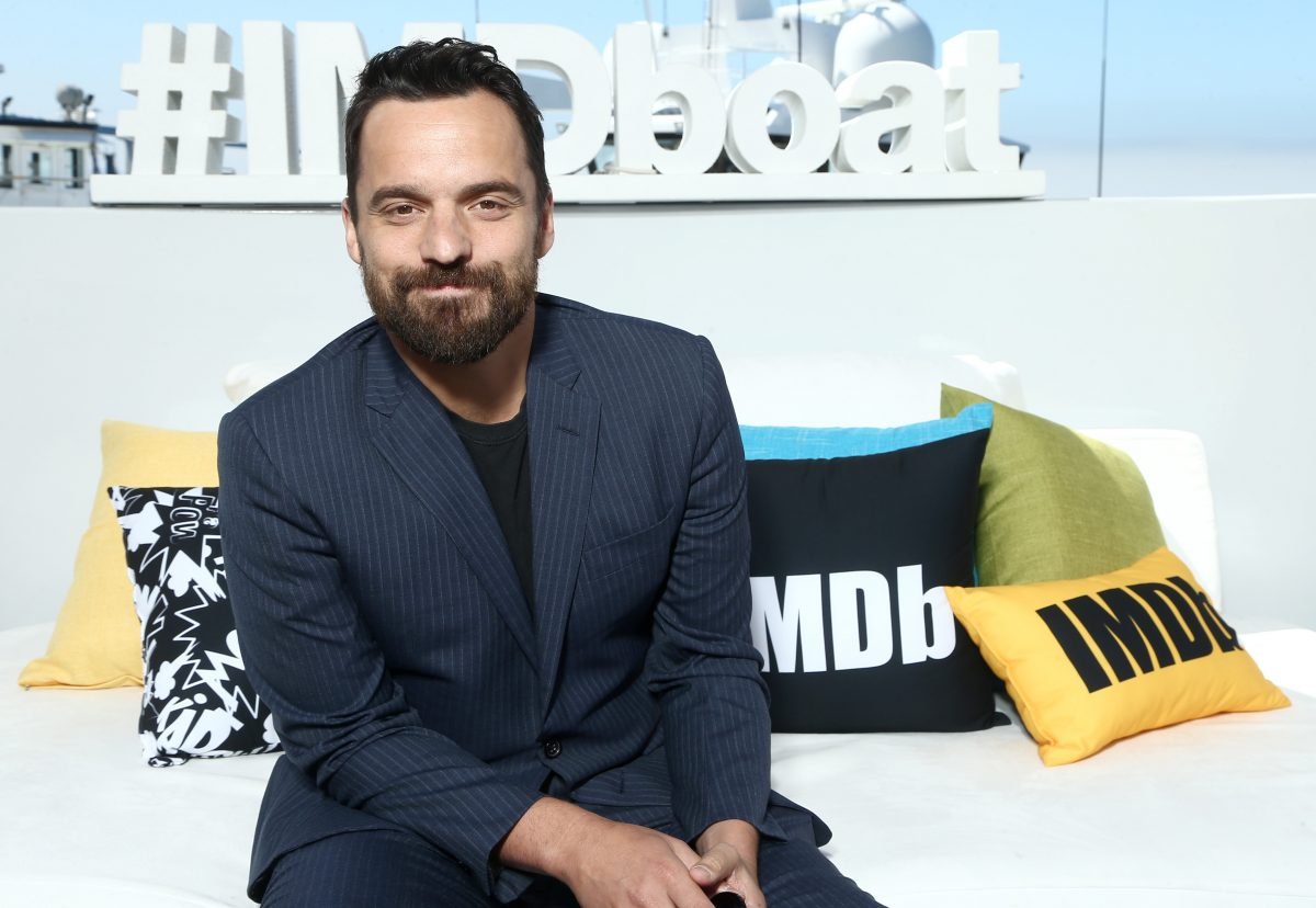 Jake Johnson smiles in front of imbd sign and pillows