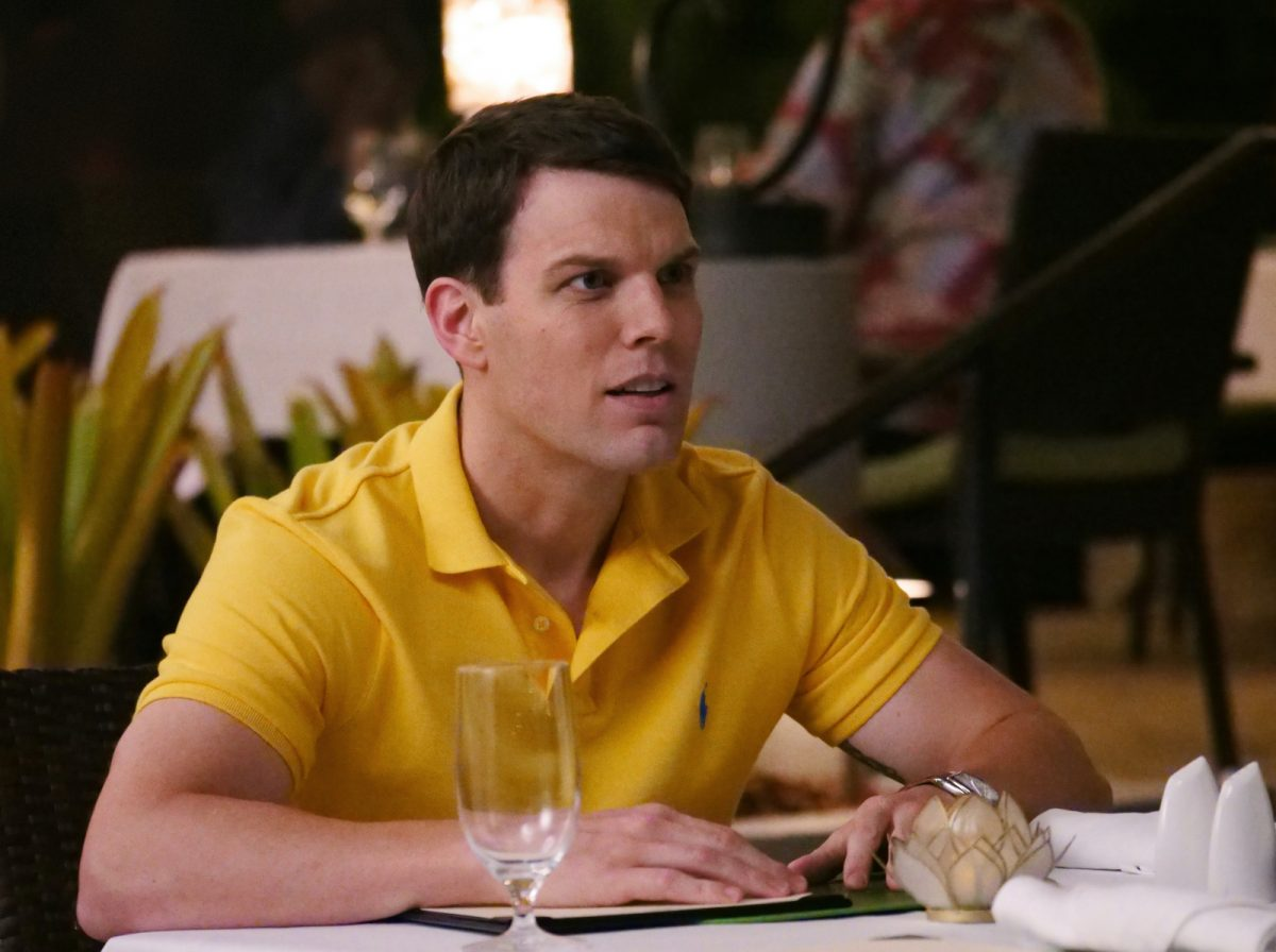 Jake Lacy as Shane in HBO's 'The White Lotus.' He's wearing a yellow polo shirt and leaning on a dinner table, which has a white table cloth and is set with utensils and glasses.