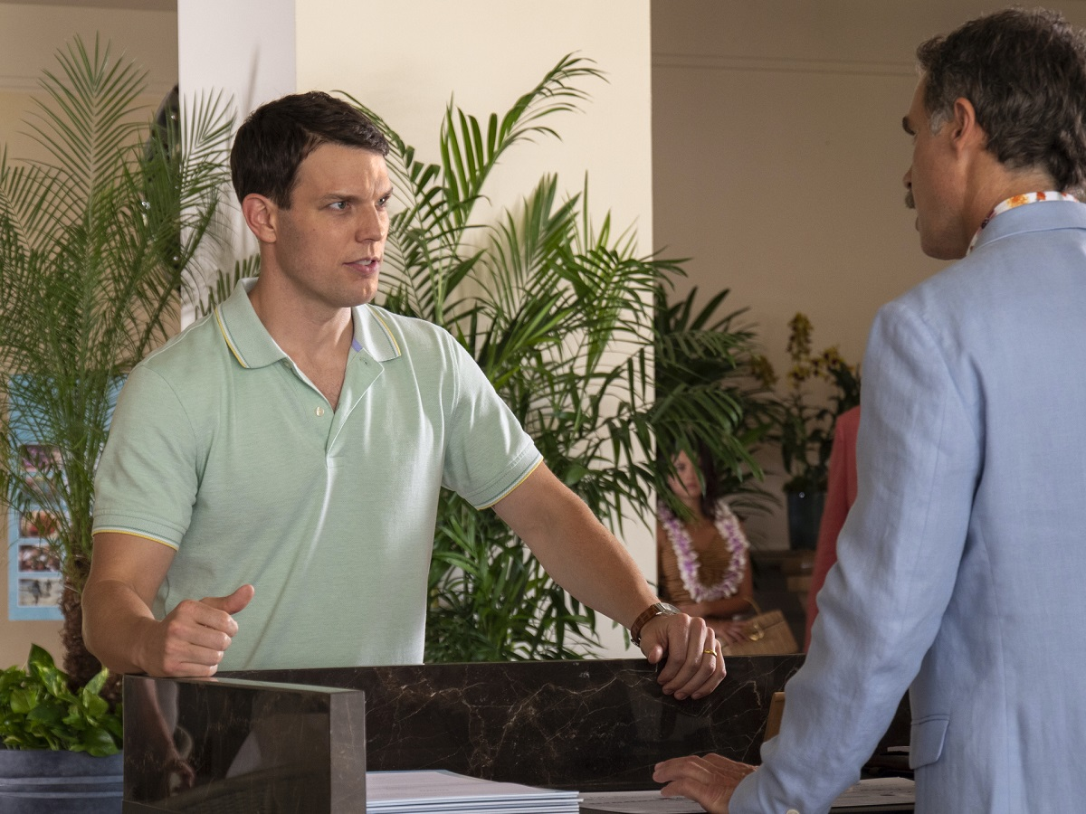 Jake Lacy in a teal shirt speaks to Murray Bartlett in a blue suit in 'The White Lotus.'