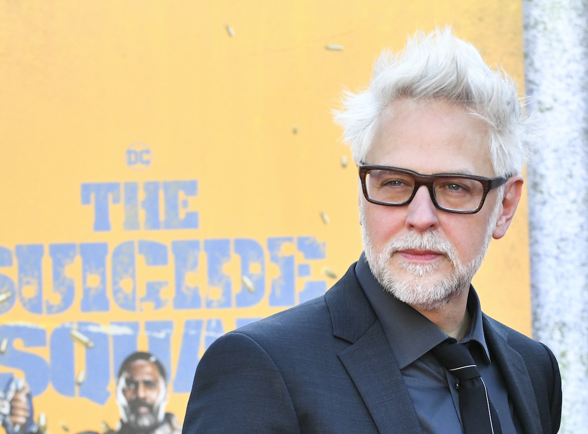 James Gunn wears a suit and poses in front of 'The Suicide Squad' artwork