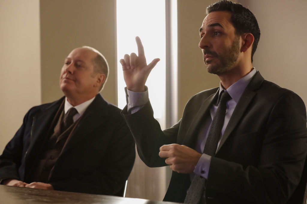 James Spader as Raymond 'Red' Reddington sits next to Amir Arison as Aram Mojtabai who is signing with ASL. They are both wearing dark suits and ties.