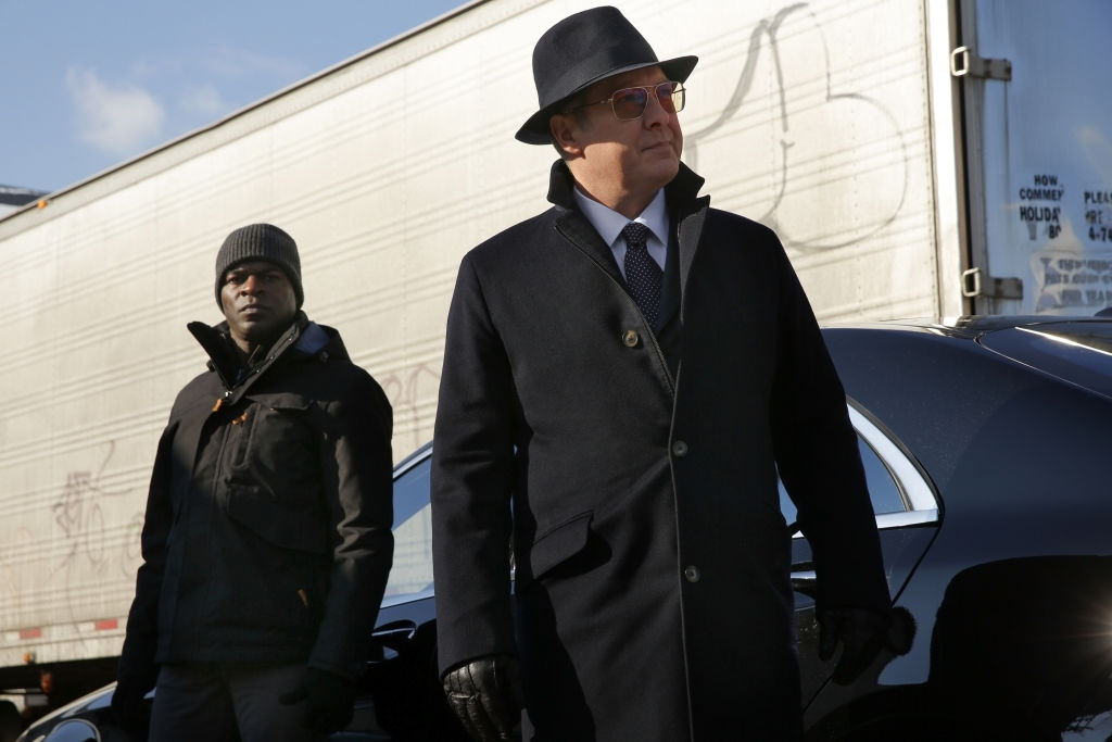 Hisham Tawfiq as Dembe Zuma stands outside next to James Spader as Raymond 'Red' Reddington. Both men are dressed in suits and overcoats.