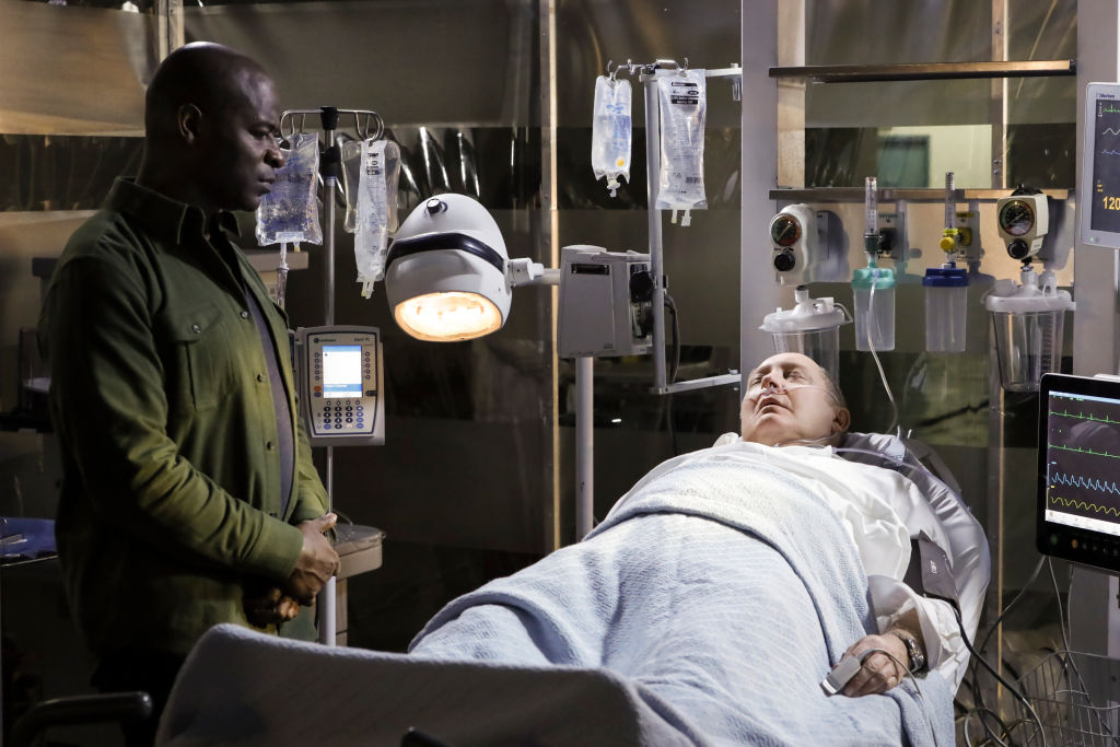 Hisham Tawfiq as Dembe Zuma stands next to an ailing James Spader as Raymond 'Red' Reddington who lies in a hospital bed connected to machines.
