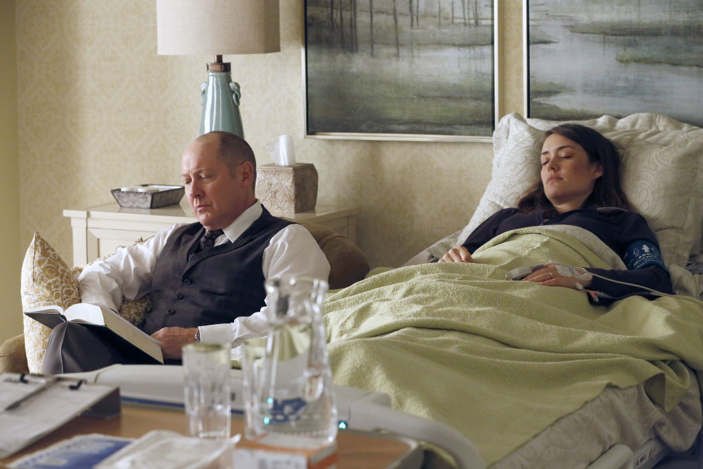 James Spader as Raymond 'Red' Reddington sits next to a hospitalized and sleeping Megan Boone as Elizabeth Keen.