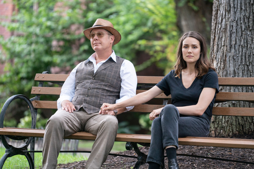 James Spader as Raymond 'Red' Reddington, Megan Boone as Elizabeth Keen sit on a bench outside together, holding hands.