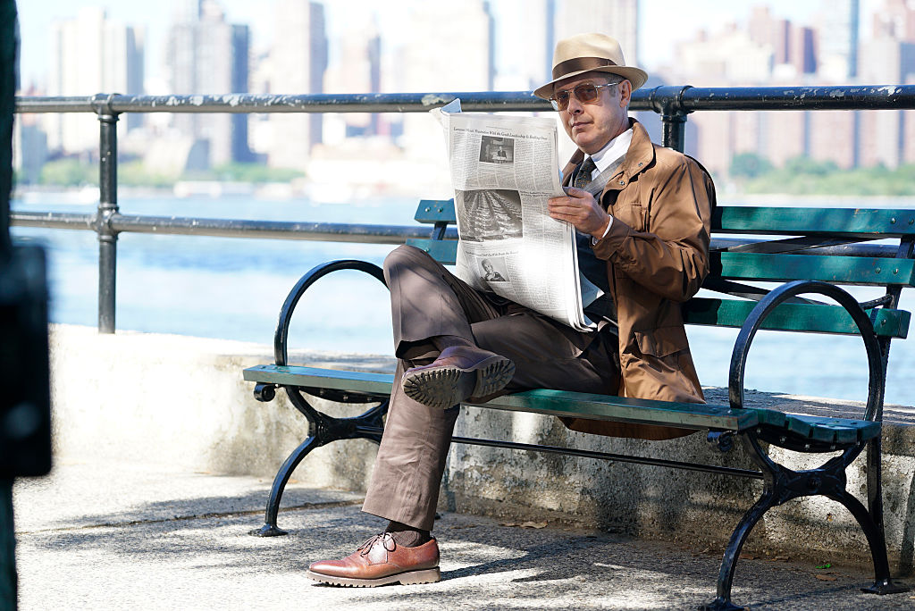 James Spader as Raymond 'Red' Reddington  sits on a bench while reading a newspaper. He's dressed in a brown suit, fedora, and sunglasses.