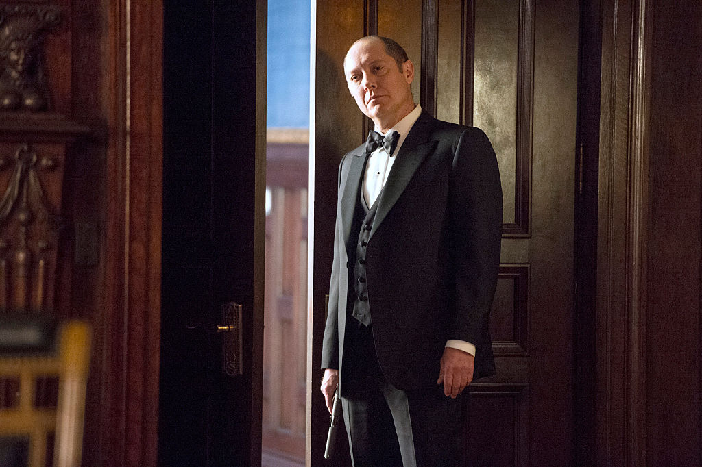 James Spader as Raymond 'Red' Reddington  stands in a dark suit with a gun in his right hand, at his side.