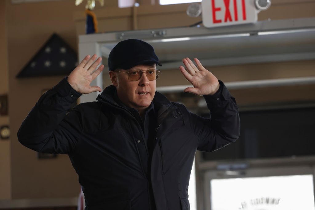 James Spader as Raymond 'Red' Reddington stands with his hands up to surrender. He's wearing a dark coat and hat and tinted glasses.